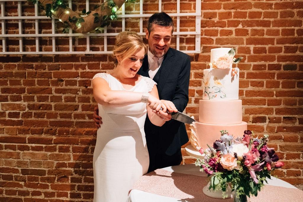 Cutting wedding cake peach wedding Haughley Park Barn suffolk wedding cake