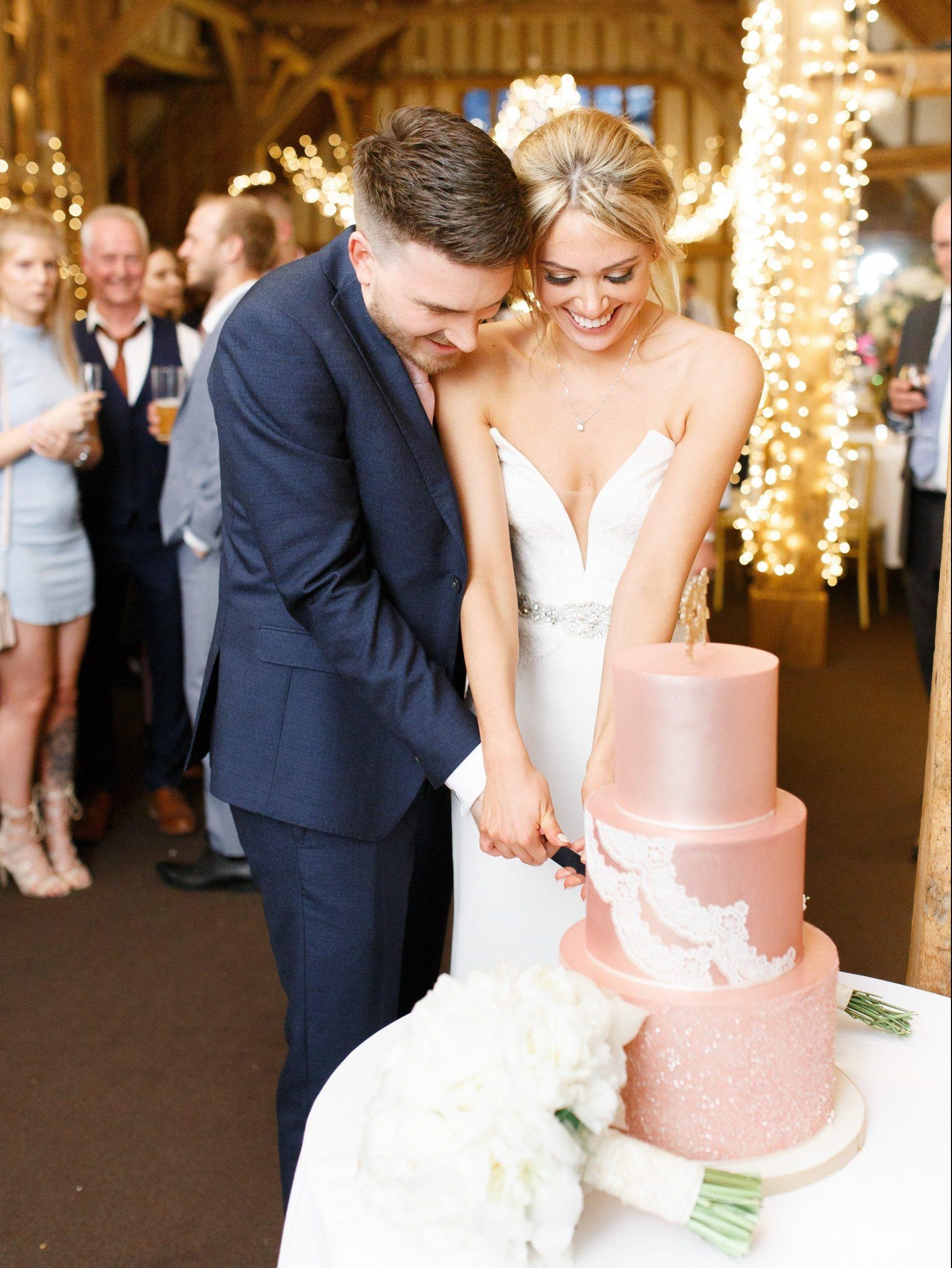 Cutting the cake pink wedding cake at Blake Hall