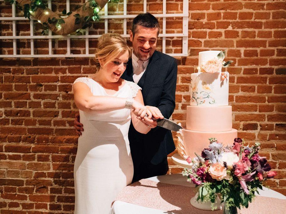 Cutting the cake peach pink wedding cake sugar flowers Haughley Park Barn Suffolk Wedding Cake